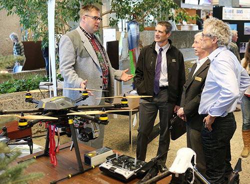 In 2015, GIS Day at Selkirk College focused on unmanned aerial vehicles. Dr. John Church (left) speaks with Selkirk College President Angus Graeme (middle left) and Vice President of Education & Students Neil Coburn (middle right) in The Pit at the Castlegar Campus.