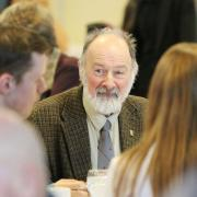 Former Selkirk College instructor and longtime donor Dr. Peter Wood speaks with students at his table.
