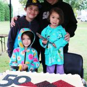Selkirk College Vice President of College Services/CFO Gary Leier cut the ceremonial cake during the Saturday morning Homecoming Weekend festivities with the assistance of his grandchildren (L-R) Yuta, Anna and Julia Covington.