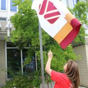 Selkirk College Campus Manager Holly Steenvoorden raises the Selkirk College flag that was made by alumna Mary Vanness for the Homecoming Weekend. In 1967, Mary (then Hutchinson) made the first Selkirk College flag out of a bedsheet and it was used in The Great Trek.