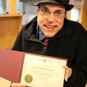 Selkirk College alumnus Cody Odell Simmons proudly shows off his post-secondary certificate.