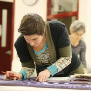 Student Miriam Popopini transfers her patterns to fabric for her final project.